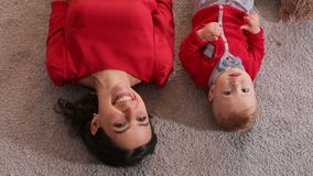 Top view of mother and her little son who lie on the fluffy carpet of the house. Top view of the young woman and her little son who lie on the fluffy carpet of stock video