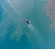 Top view of motion tugboat at azure water with a spot of oil. Stock Image