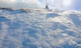 Ski piste of compacted snow from chairlift. Top view of the mountain slope with compacted snow from chairlift on ski resort on a windy winter day Stock Image