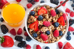 Top view of muesli with red fruits and orange juice. Stock Image
