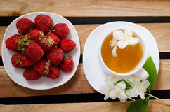 Top view of a mug of herbal tea and jasmine flowers, a plate with strawberries on wooden plates Stock Photo