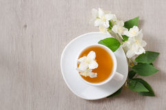 Top view of a mug of herbal tea and jasmine flowers on a wooden table, space for text Stock Image