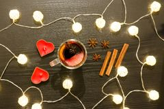 Top view on a mug of mulled wine with spices, candles and lanter. Ns. Black background Royalty Free Stock Images