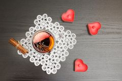Top view on mulled wine with spices. Candles in the shape of a h. Eart.  Black wood background Stock Photo