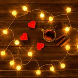 Top view of mulled wine with spices, candles in the shape of a heart, cinnamon sticks, star anise on a wooden table. Garland of la. Nterns Stock Photo