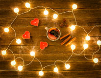 Top view of mulled wine with spices, candles in the shape of a heart, cinnamon sticks, star anise on a wooden table. Garland of lanterns Stock Photo