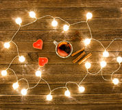 Top view of mulled wine with spices, candles in the shape of a heart, cinnamon sticks, star anise on a wooden table. Garland of la. Nterns Stock Photography