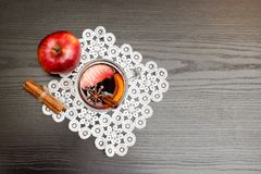 Top view on mulled wine with spices. Cinnamon sticks and apple. Black wood background Stock Photography