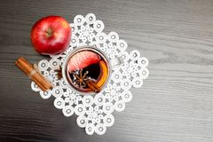 Top view on mulled wine with spices. Cinnamon sticks and apple. Black wood background Stock Photos