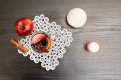 Top view on mulled wine with spices. Cinnamon sticks and apple. Black wood background Royalty Free Stock Image