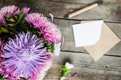 Top view Multicolor aster flowers bouquet, pen, blank white greeting card and craft paper envelope on rustic wooden table.. Postca. Rd mock up. Autumn flowers Stock Image