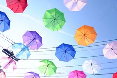 Top view multicolored umbrellas hanging on a wire against blue sky white clouds in bright day and electricity lines background. Top view multicolored umbrellas stock photo