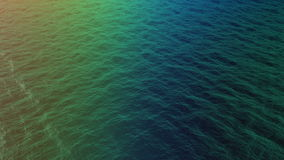 Top view of multicolored water waves on sunset stock video footage