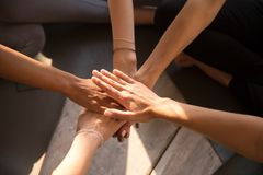 Top view of women stack hands engaged in teambuilding activity. Top view of multiracial women sit in circle on training put hands in stack showing mutual support royalty free stock photo