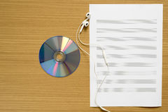 top view of music staff paper dvd dish and earphone Royalty Free Stock Photos