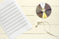 top view of music staff paper earphone and dvd disc Royalty Free Stock Photo