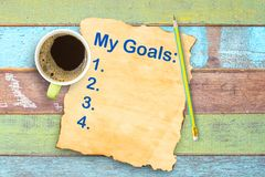 Top view My goals list on old paper and coffee cup,pencil on off. Ice wooden table. Space for use and design Royalty Free Stock Photo