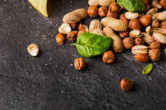 Top view of nacho chip, roasted peanuts, brown hazelnuts and cracked pistachios with basil on a black background. Stock Images