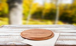 Top view napkin and pizza desk on wooden table with blurred park background, mock up royalty free stock images