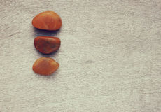 Top view of natural stones on old wooden table. filtered image . room for text. Royalty Free Stock Photos