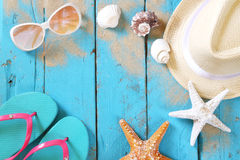 Top view of nautical concept. With fedora hat, sunglasses, flip flops and seashells on aqua wooden background stock photos