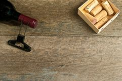 Top view, of neck of a red bottle of french wine and opener. Top view, close up of the neck of a french wine bottle with a vintage cork screw and a wood box with Stock Photos