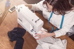 Top view of needlewoman stitching fabric on sewing machine at workplace in studio.  Stock Image
