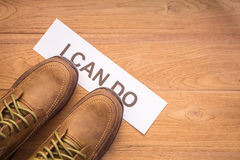 Top view new men shoes step on word I CAN DO in white crumpled Stock Photos