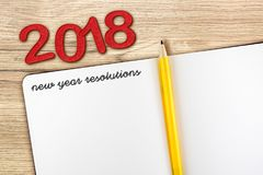 Top view of 2018 new year resolution with blank open notebook an. D yellow pencil on wooden table top,Mock up for adding your content or design stock photography