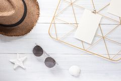 Top view note pad clip frame and summer straw hat with sunglasses on white wood table.summer vacation background