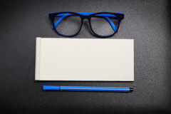Top view note paper with blue eye glasses and blue pen Stock Images