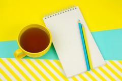Notebook with blank white paper sheet, pencils and cup of tea. Top view notebook with blank white paper sheet, pencils and cup of tea royalty free stock photo