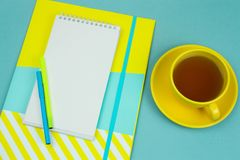 Notebook with blank white paper sheet, pencilsand cup of tea on a blue background. Top view notebook with blank white paper sheet, pencilsand cup of tea on a royalty free stock photography