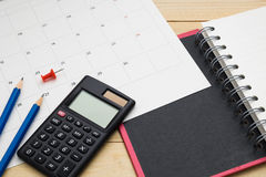 Top view notebook ,calculator,pencil,pin and calendar put on woo Royalty Free Stock Photo
