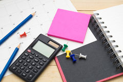 Top view notebook ,calculator,pencil,post it note and calendar p Stock Photos