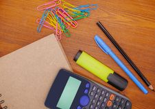 Top view notebook,calculator and stationery on brown wooden table. Business,education concept royalty free stock photo