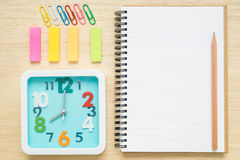 Top view notebook, clock, paper clips on wooden desk Stock Photo