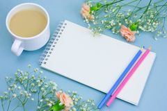 Notebook with empty white paper sheet ,colored pencils,coffe with cream cup and floral frame on a pastel blue background. Top view notebook with empty white stock photos