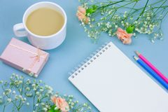 Notebook with empty white paper sheet ,colored pencils,coffe with cream cup and floral frame on a pastel blue background. Top view notebook with empty white royalty free stock image