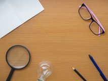 Top view of notebook, light bulb, pink glasses, Magnifying glass pen and pencil on wooden table with center copy space royalty free stock photo
