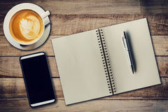 Top view notebook, pen, coffee cup, and phone on wood table, Vin Royalty Free Stock Image