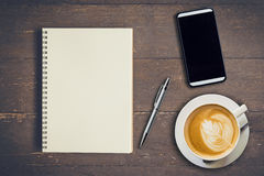 Top view notebook, pen, coffee cup, and phone on wood table Stock Photos