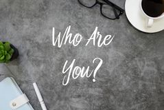 Top view of notebook,plant,pen,coffee and glasses on grey grunge floor written with question & x27; Who Are You. Personality identity answer curious confusion royalty free stock images