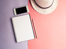 Top view of notebook, smartphone, hat on violet purple backgroun Stock Image