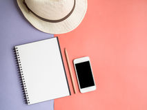 Top view of notebook, smartphone, hat on violet purple backgroun Royalty Free Stock Images