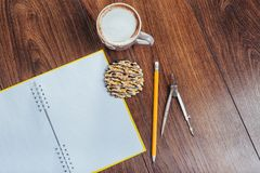 Top view of notebook, stationery, drawing tools and a few cups coffee. royalty free stock photos