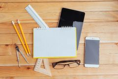 Top view of notebook, stationery, drawing tools and a few glasses. improvise. royalty free stock images