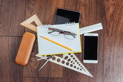 Top view of notebook, stationery, drawing tools and a few glasses. improvise. royalty free stock photo