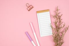 Top view of notebook stationery and flower on pink background stock photography