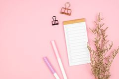 Top view of notebook stationery and flower on pink background royalty free stock photo